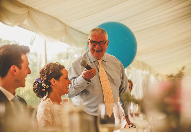 The brides father smiles as he delivers his speech