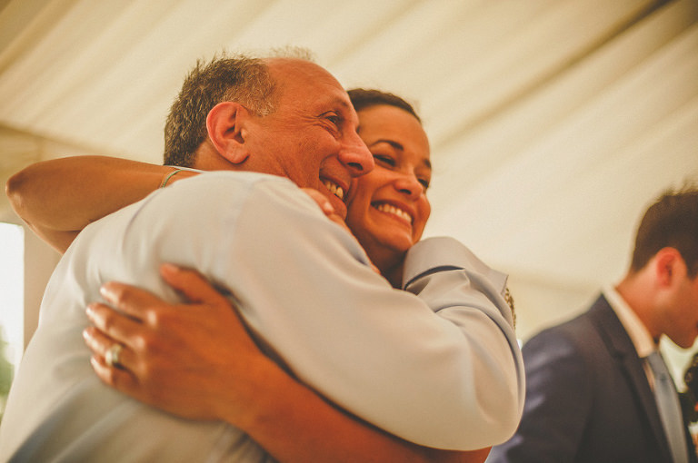 The brides sister and the grooms father embrace each other