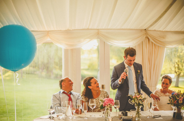 The groom stands at the top table and talks into a microphone