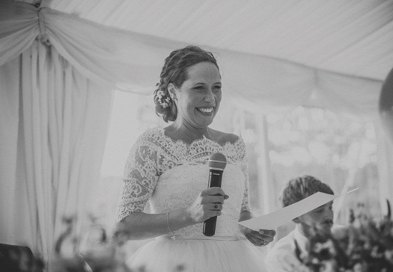 The bride smiles as she delivers her speech