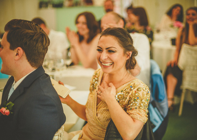 One of the wedding guests laughs as she listens to the best mans speech