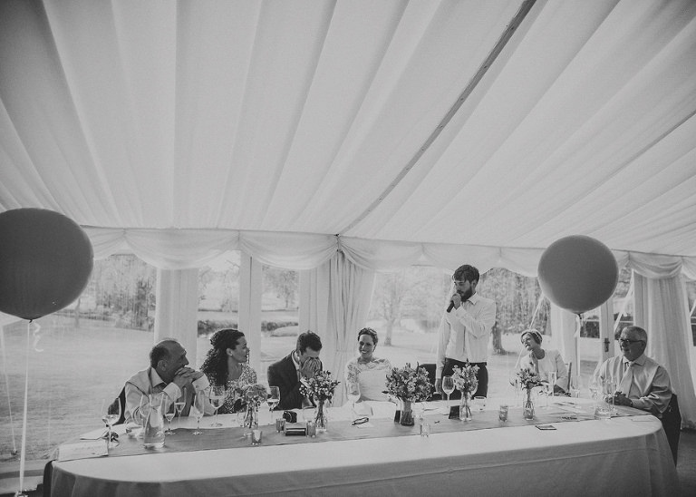 The best man looks at the groom as he stands at the top table in the marquee