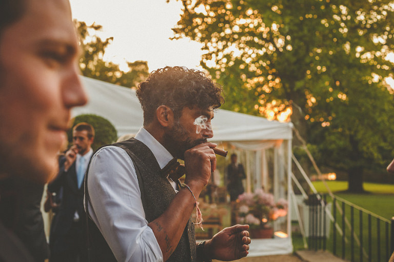 A wedding guest exhales a cigar in the garden as the sun goes down