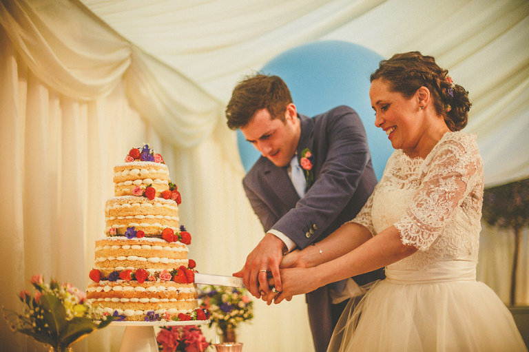 The bride and groom cut the cake in the marquee