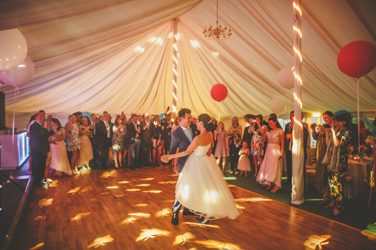 The bride and grooms first dance on the dancefloor in the marquee