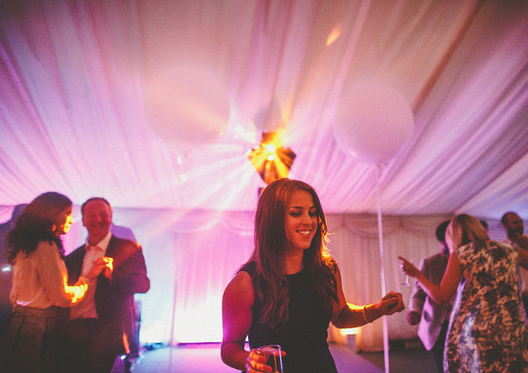 A wedding guest smiles as she dances on the dancefloor in the marquee
