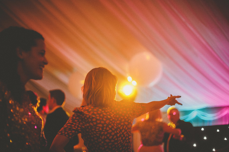 A wedding guest dances with friends in the marquee
