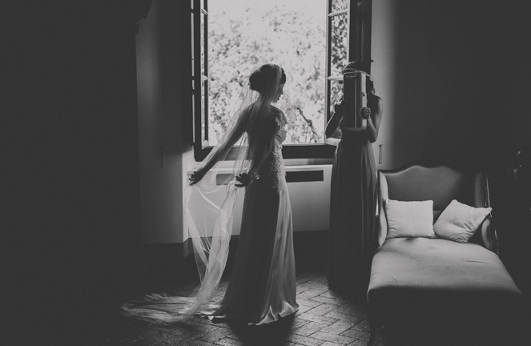 The bride looks in the mirror which is held by a bridesmaid