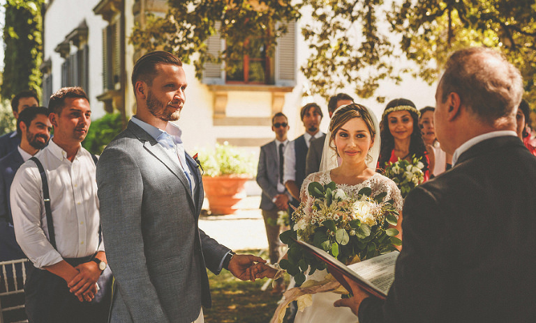 The bride and groom during their ceremony in the gardens of the villa in San Casciano