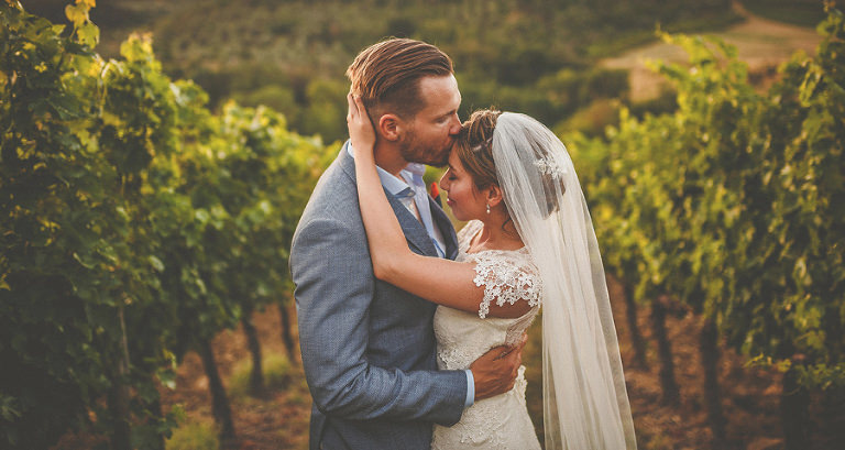 The groom kisses his bride inbetween the olive groves on the outskirts of San Casciano