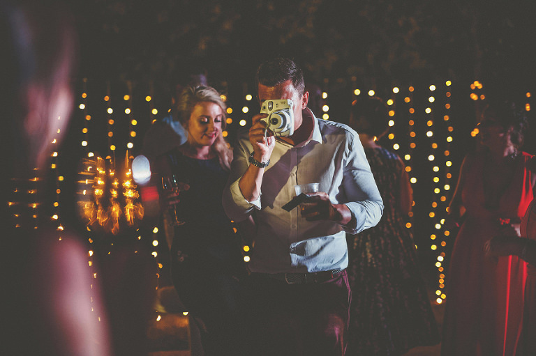 One of the wedding guests takes a polaroid photograph of people dancing