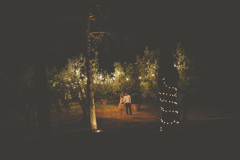 A couple go for a walk around the gardens of the villa