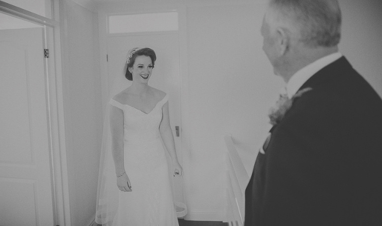 The bride and her father meet for the first time in her wedding dress