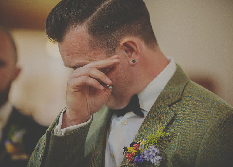 The groom raises his right hand and wipes a tear from his left eye during the ceremony