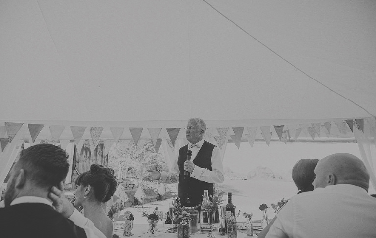 The brides father stands up and delivers his speech to the wedding party