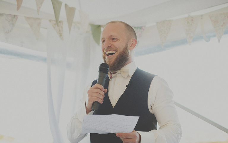 The best man laughs as he reads out his speech in the marquee