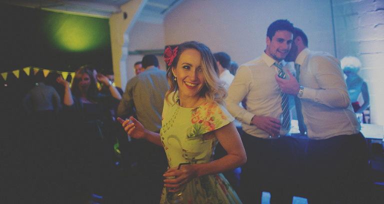 A lady on the dancefloor with an alcoholic drink in her hand