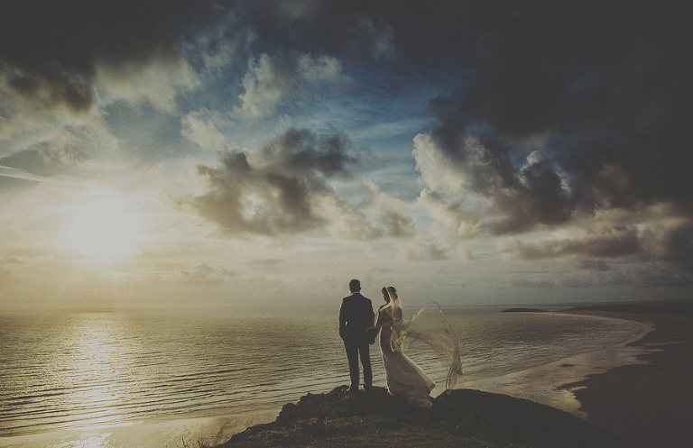 The bride and groom stand above Rhosilli bay beach while the sun goes down
