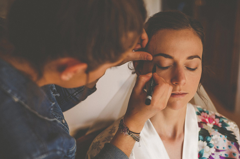 The make up artist applies mascara to the brides right eyelashes