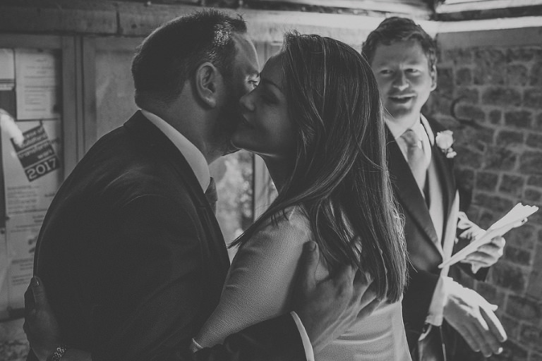 A wedding guest kisses an usher on the cheek entering the church