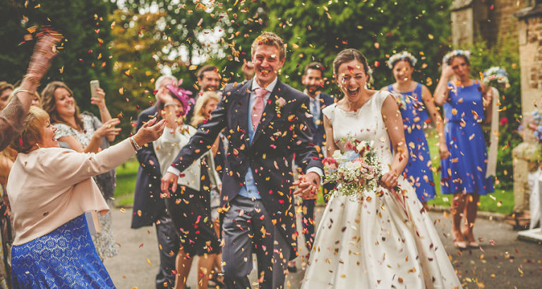 The bride and groom are showered with confetti after the ceremony