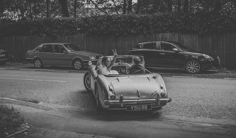 The bride and groom leave St. Lukes church in their vintage MG car