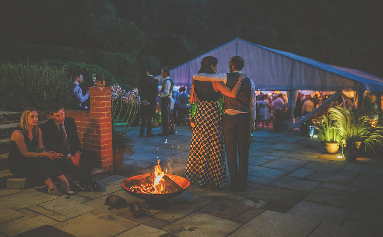 Wedding guests sit around a firepit outside the marquee