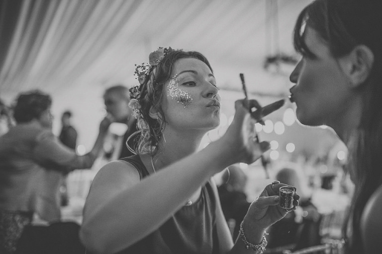 The brides sister painting glitter on wedding guests faces