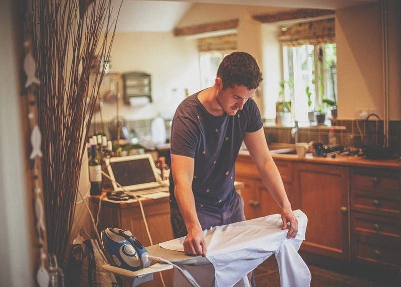 The brides brother irons his shirt in the kitchen