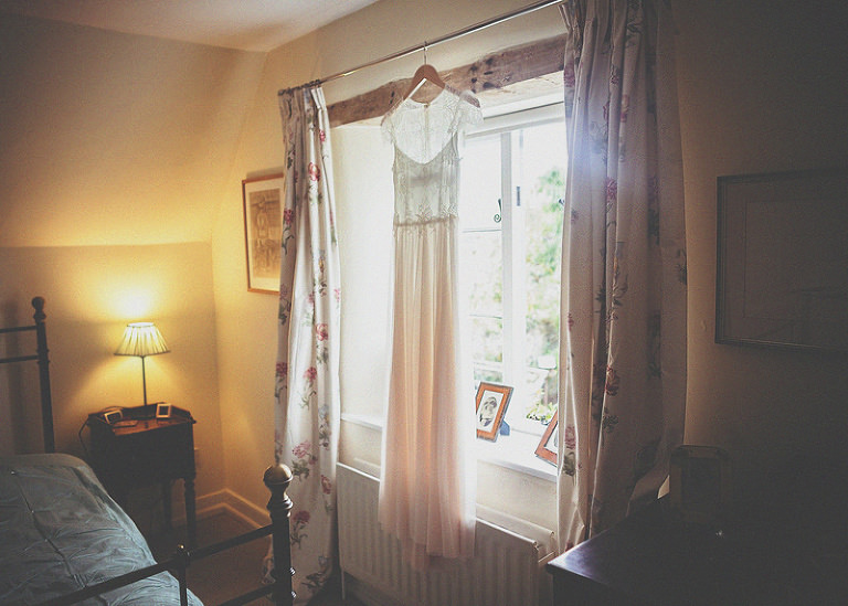 The brides dress hangs from the curtain rail of her mothers bedroom