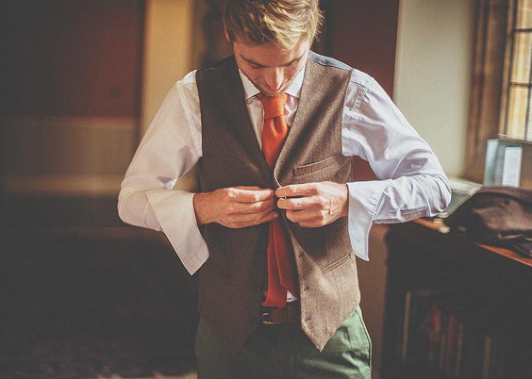 The groom fastens his waistcoat