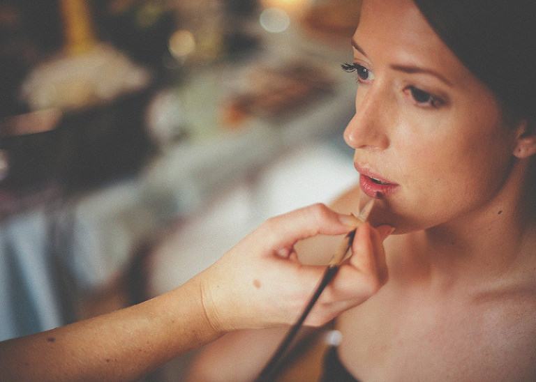 The make up artist applies lipstick to the lips of the bride
