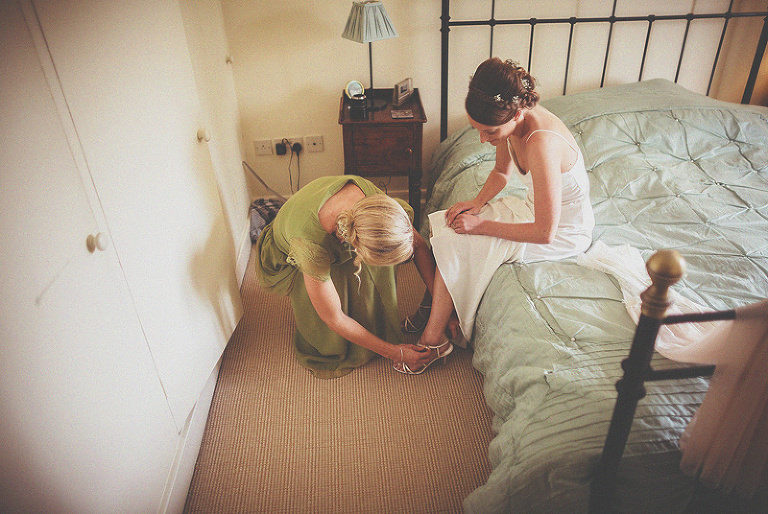 A bridesmaid fastens the buckle of the brides shoe as the bride sits on her mothers bed
