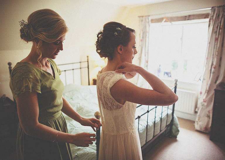 A bridesmaid fastens the back of the brides dress