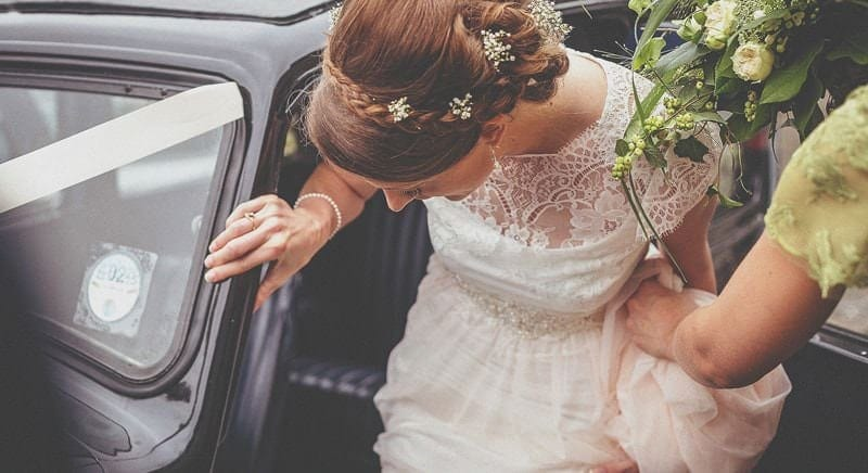 The bride is helped into the car by one of the bridesmaids