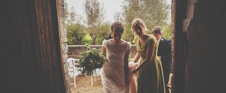 The bride, her father and a bridesmaid enter the doorway at Almonry Barn
