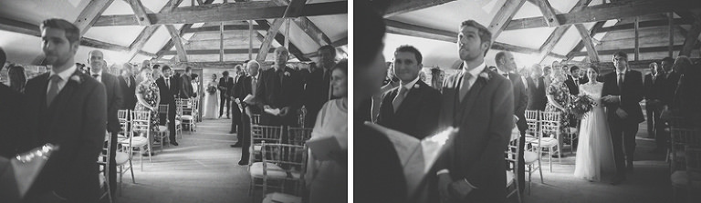 The bride and her father walk up the aisle together at Almonry Barn