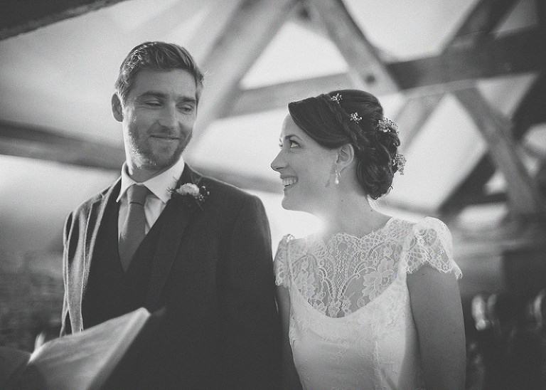 The bride and groom look at each other and smile at Almonry Barn