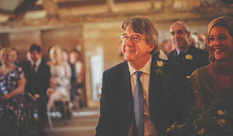 The brides father smiles during the wedding ceremony at Almonry Barn