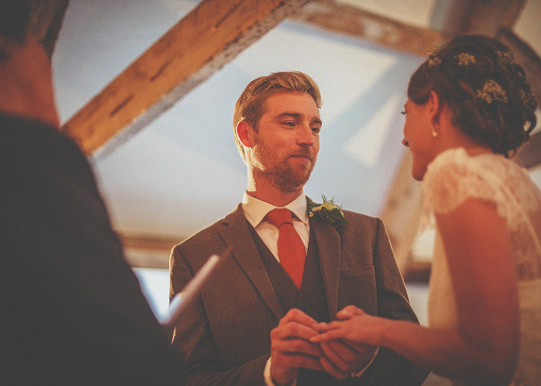 The groom places a ring on the finger of the bride during the wedding ceremony at Almonry Barn