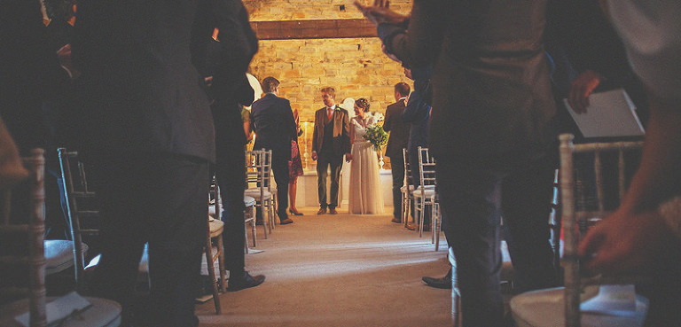 The bride and groom get ready to walk down the aisle together at Almonry Barn