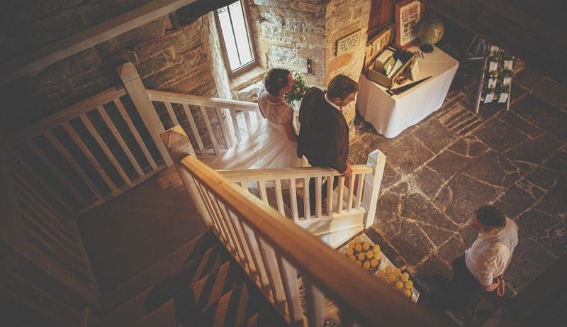 The bride and groom walk down the staircase at Almonry Barn
