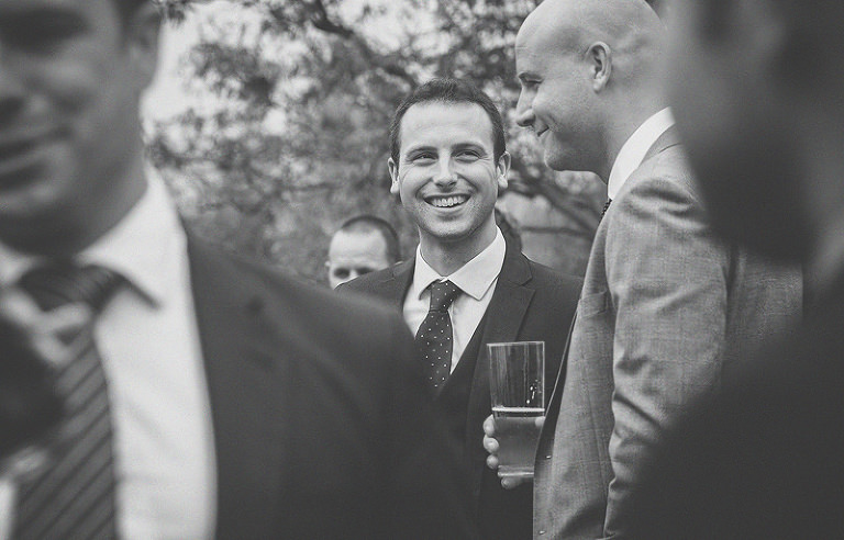 A wedding guest smiles at his friend