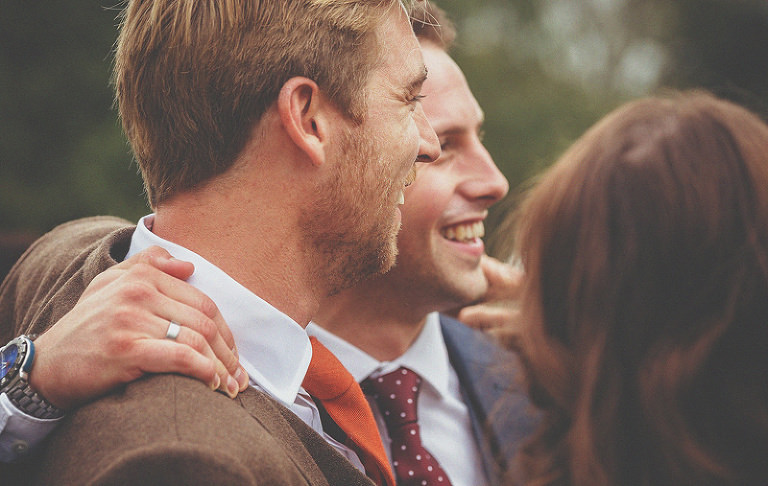 A wedding guest puts his arm around the groom and smiles