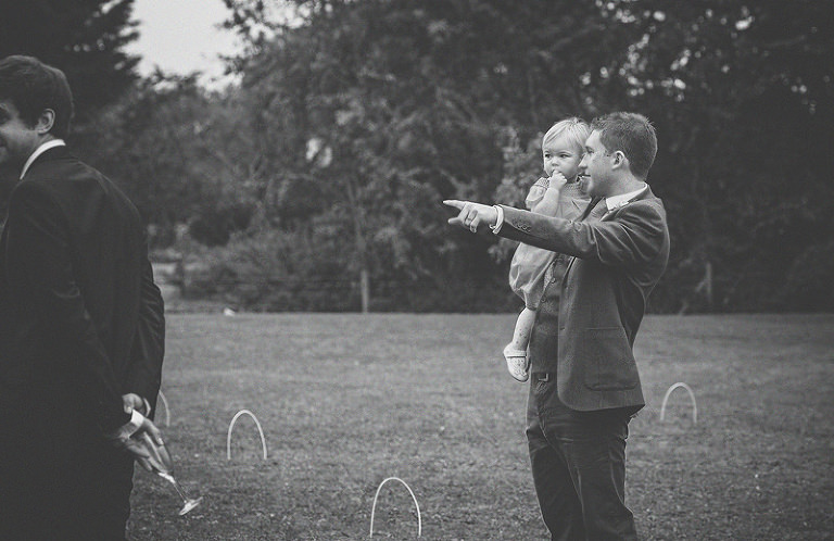 A wedding guest points to the barn and looks at his daughter as he holds her in his arms