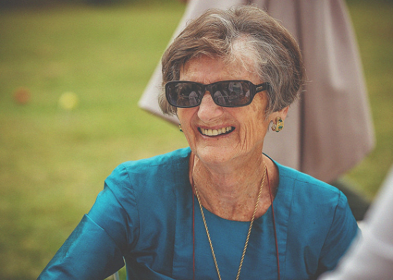 A lady with sunglasses on smiles outside at Almonry Barn