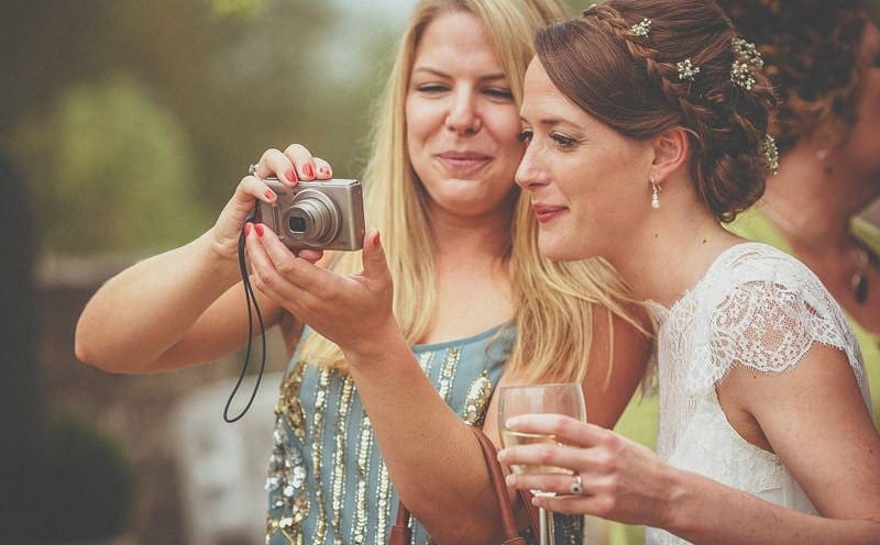 A wedding guest shows a photograph to the bride