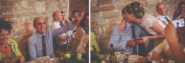 The bride walks across the barn and embraces a wedding guest