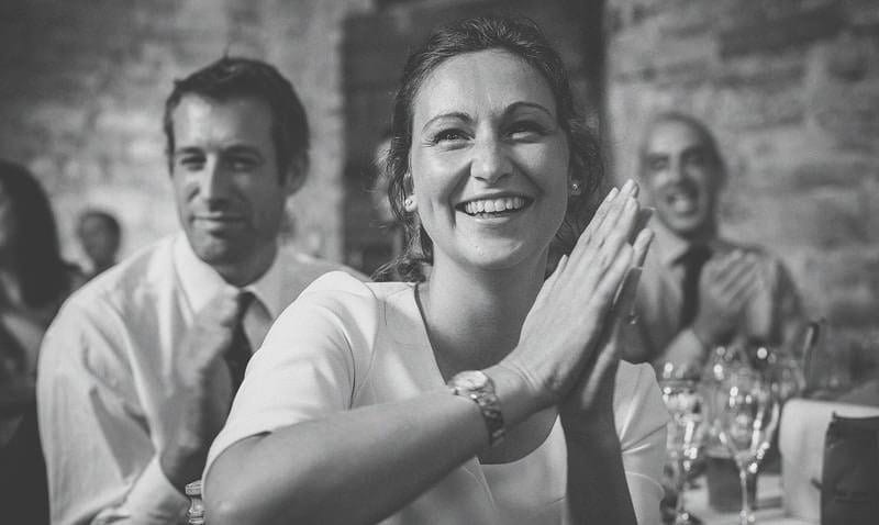 A lady smiles and claps during a wedding speech in the barn