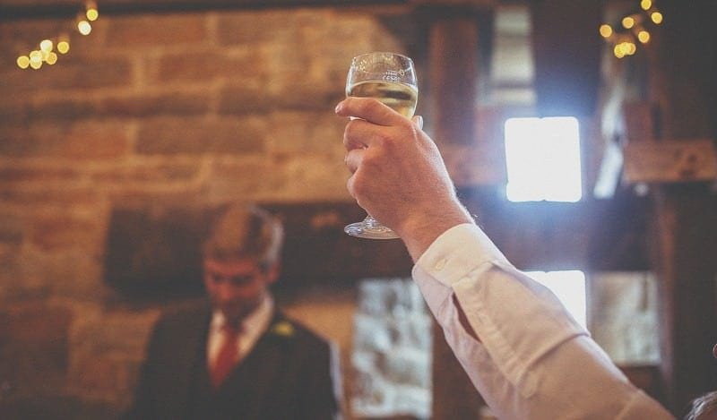 A glass of champagne is raised in the air during a wedding speech in the barn